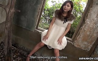 Depraved slim Japanese chick stripteases in deserted digs and flashes hairy pussy
